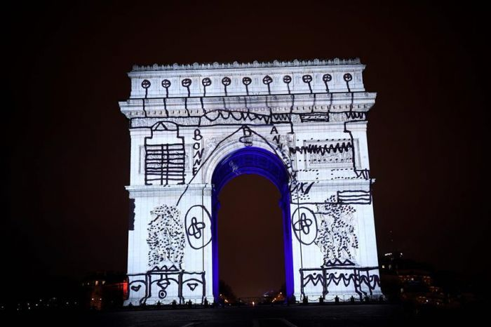 2016年12月31日夜,在法国巴黎,一名儿童的绘画作品被映在该市标志性建筑凯旋门上。