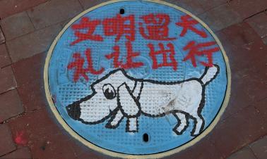 Beijing manhole art promotes proper dog ownership